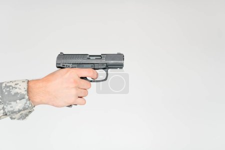 cropped shot of male soldier holding gun on grey backdrop