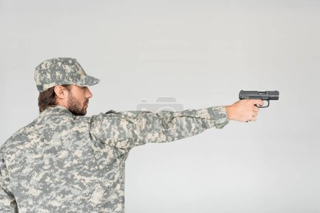 side view of male soldier in military uniform holding gun isolated on grey