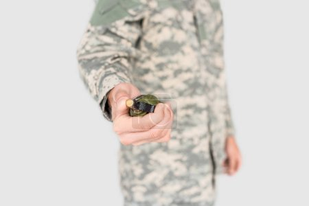 cropped shot of soldier holding grenade in hand isolated on grey