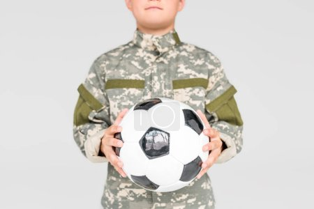 partial view of kid in military uniform with soccer ball in hands isolated on grey