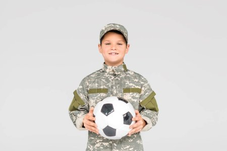 portrait of smiling kid in military uniform with soccer ball in hands isolated on grey