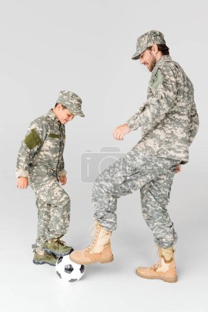 side view of father and son in military uniforms playing soccer on grey background