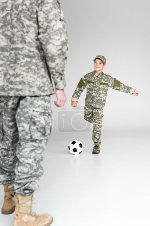 partial view of father and son in military uniforms playing soccer on grey background