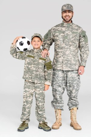 smiling family in military uniforms with soccer ball looking at camera on grey background