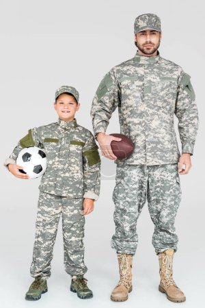 family in military uniforms holding soccer and rugby balls on grey background