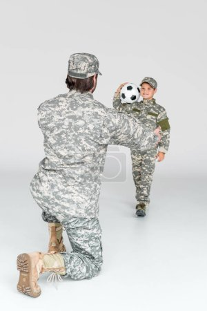 partial view of soldier with outstretched arms and smiling kid in camouflage clothing with soccer ball on grey background