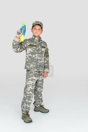 little boy in military uniform holding toy water gun on grey background