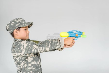 side view of boy in camouflage clothing with toy water gun isolated on grey