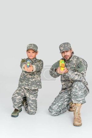 father and son in military uniforms with toy water guns on grey background