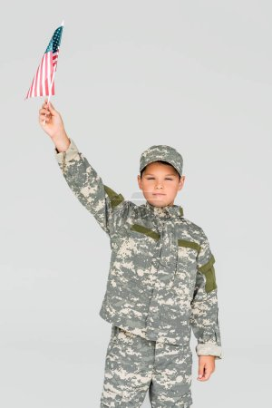 portrait of little boy in camouflage clothing holding american flagpole in hand isolated on grey