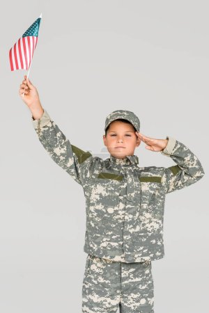 portrait of boy in camouflage clothing saluting while holding american flagpole in hand isolated on grey