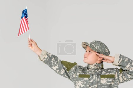 portrait of boy in camouflage clothing saluting and looking at american flagpole in hand isolated on grey