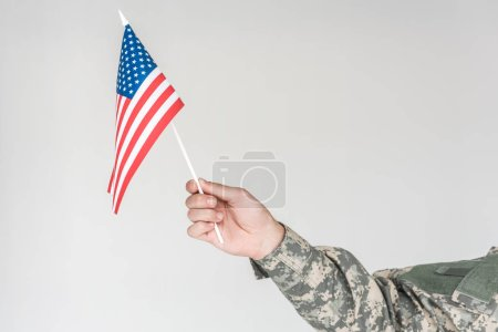 partial view of boy in camouflage clothing holding american flagpole in hand isolated on grey