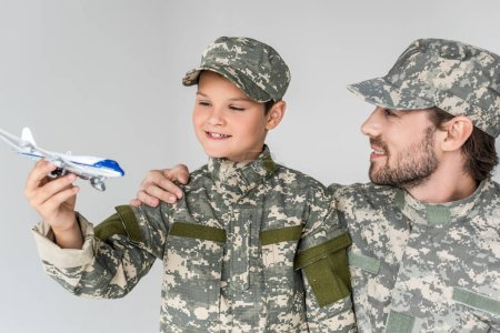 portrait of father and son in military uniforms with toy plane isolated on grey