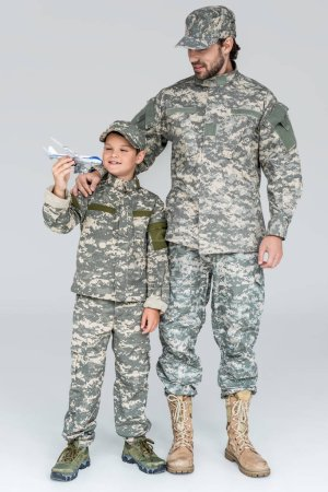 family in military uniform with toy plane on grey background