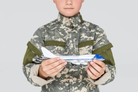 partial view of little boy in military uniform with toy plane in hands isolated on grey
