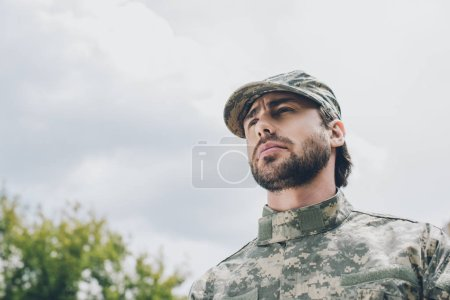 portrait of confident soldier in military uniform with cloudy sky on background