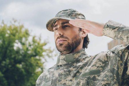 Photo pour Portrait d'un soldat confiant en uniforme militaire avec ciel nuageux en arrière-plan - image libre de droit