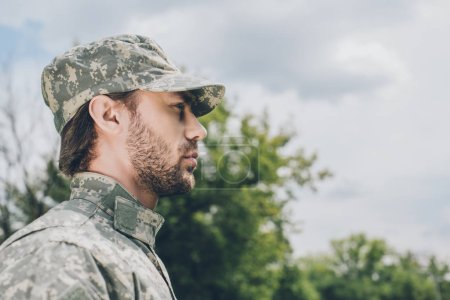 side view of confident soldier in military uniform with cloudy sky on background