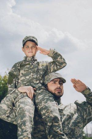 Photo pour Vue à angle bas de la famille en uniforme militaire saluant avec ciel nuageux sur toile de fond - image libre de droit