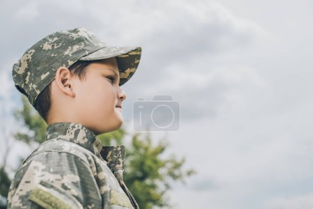 side view of little boy in camouflage clothing with cloudy sky on backdrop