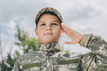 portrait of little boy in camouflage clothing saluting with cloudy sky on backdrop