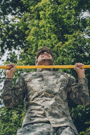 low angle view of soldier in military uniform pulling himself up on crossbar