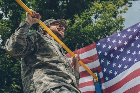 low angle view of soldier pulling himself up on crossbar with american flag on backdrop