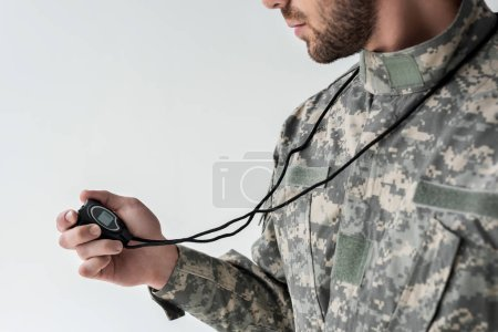 partial view of soldier in military uniform with stop watch isolated on grey
