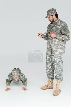 soldier in military uniform with timer and whistle controlling time while son doing push ups on grey background