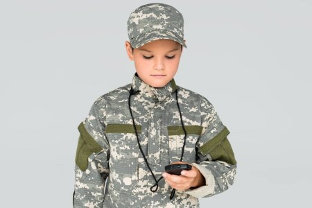 portrait of kid in military uniform with stop watch in hand isolated on grey