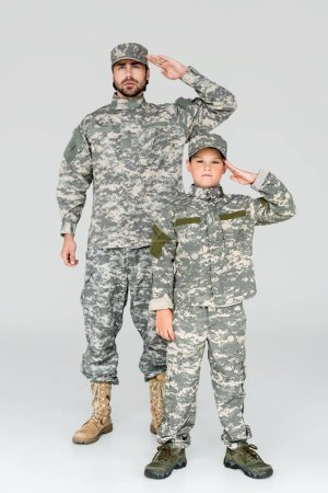 family in military uniforms saluting and looking at camera on grey background