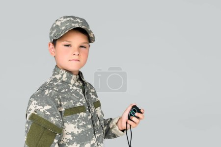 portrait of kid in military uniform with stop watch in hand looking at camera isolated on grey