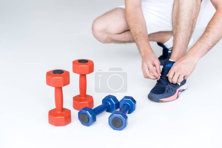 Photo for Partial view of man tying shoelaces near red and blue dumbbells on grey backdrop - Royalty Free Image