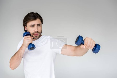 portrait of man in white shirt with blue dumbbells in hands exercising on grey backdrop