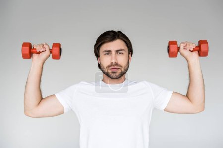 Photo for Portrait of man in white shirt with red dumbbells in hands exercising on grey backdrop - Royalty Free Image