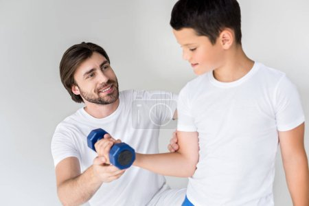 father helping little son with dumbbell to exercise on grey background