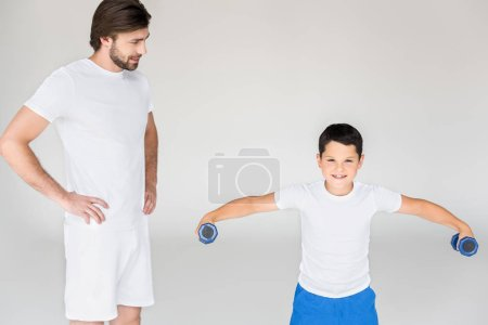 man standing akimbo and looking at son with dumbbells exercising on grey backdrop
