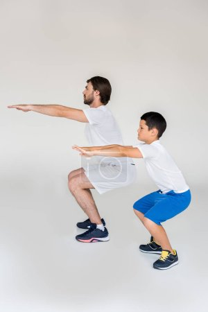 side view of boy and father squatting together on grey background