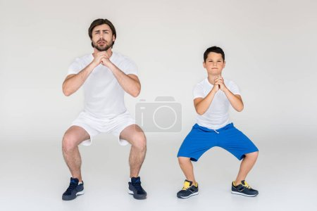 boy and father squatting together on grey background