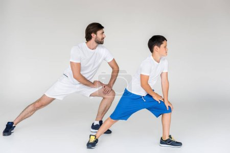father and son in white shirts stretching on grey backdrop