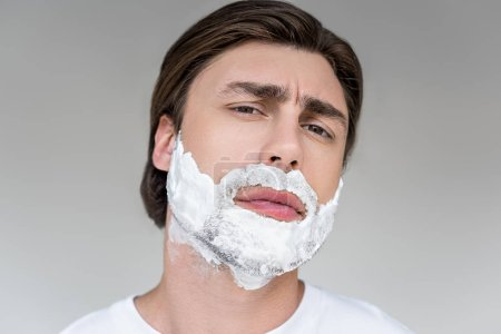 portrait of handsome man with shaving foam on face looking at camera isolated on grey