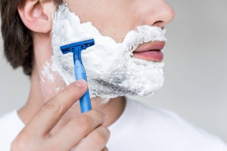 cropped shot of man with razor in hand and shaving foam on face on grey backdrop