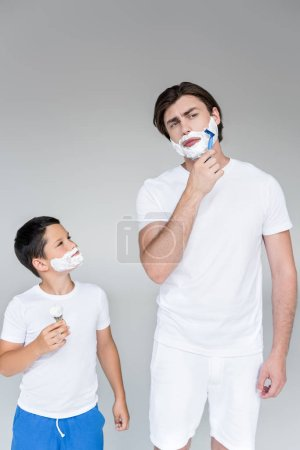 portrait of father and son with shaving foam on faces with brush and razor in hands on grey background