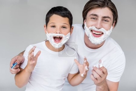 portrait of emotional father and son with shaving foam on faces isolated on grey