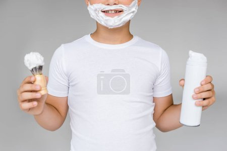 partial view of smiling preteen boy with brush, cream and shaving foam on face isolated on grey