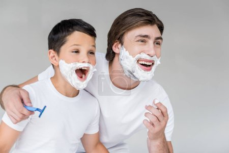 Photo for Excited father and son with shaving foam on faces isolated on grey - Royalty Free Image