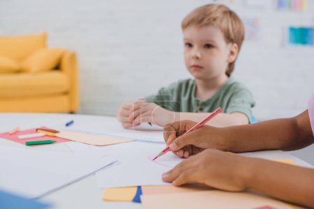 partial view of multicultural preschoolers at table with papers and pencils in classroom