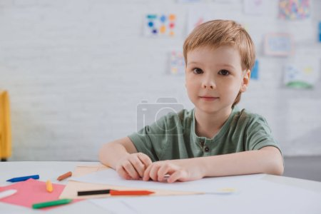 portrait of preschooler sitting at table with colorful pencils in classroom