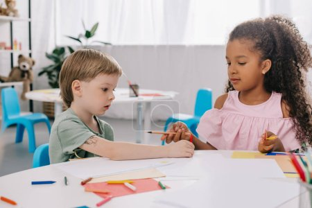 portrait of multicultural preschoolers at table with papers and pencils in classroom